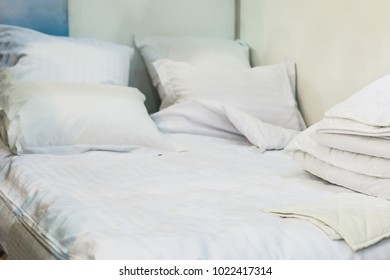 Bed maid-up with clean white pillows and bed sheets in beauty room. Close-up. Lens flair in sunlight.