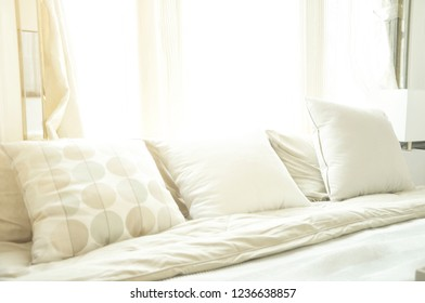 Bed maid-up with clean white pillows and bed sheets in luxury room. Close-up. Lens flair in sunlight.