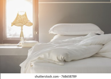 Bed maid-up with clean white pillows and bed sheets in beauty room. Close-up. Lens flair in sunlight.Close up white bedding sheets and pillow, Messy bed concept