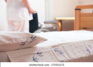 Bed at nursing home with nurse and wheelchair on background.