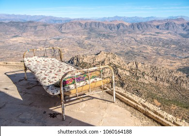 Bed outdoors sleeping at the former palace of Saddam Hussein near Duhok, Kurdistan, Iraq. Ruins of Palace, destroyed by Peshmerga army in Kurdistan Iraq mountains in background.