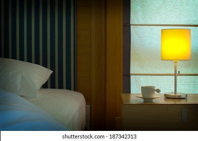 bed with a pillow, a cup of tea on the bedside table and lamp.