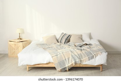 Bed with pillows and plaid in modern room interior
