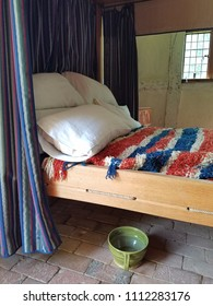 bed with pillows and red, white, and blue blanket and green chamber pot