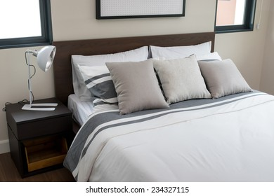 bed and pillows with white lamp on table