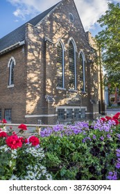 A bed of red and purple flowers in front of The Church which is partially shaded by a tree in Stouffville Ontario Canada.
