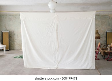 Bed sheet hanging homemade projector screen, old house rural village vintage interior