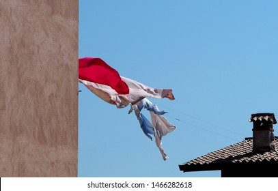 Bed sheets and clothes hanging out to dry on a clothesline between roof and wall, in a windy day
