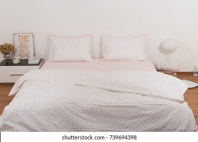 Bed with sheets, pillows and blanket. Bedroom interior
