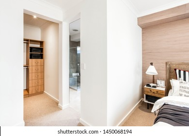 A bed with a side table with a lampshade, attached washroom adjacent to organizer shelves.