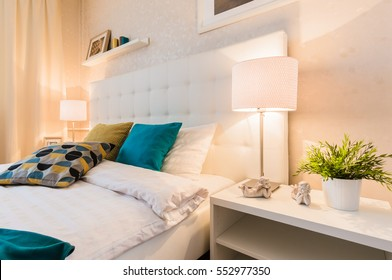 bed with soft headboard and bedside tables with lights