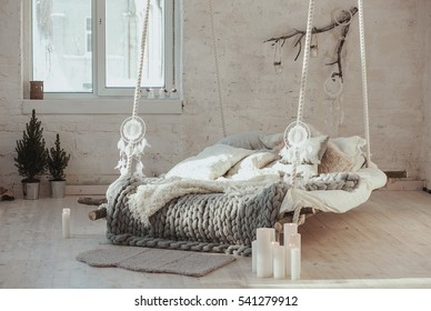 The bed suspended from the ceiling. Grey big cozy blanket knit. Scandinavian style, gray plaid, candles.