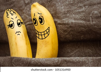 In bed, two bananas. A man flirts, offers sex, a woman opposes. Tiff, sexual problems, dissatisfaction, frigidity. Gray background, the picture is made by the author.