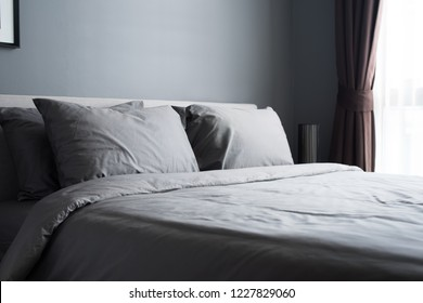 bed with two pillows. gray linen on king size bed. minimalism in hotel