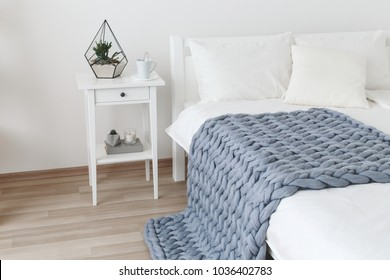 Bed with white linen and grey knitted woolen merino chunky blanket. Light stylish cozy scandinavian bedroom interior. Blanket of thick yarn. Geometric glass florarium with plants on bedside table.