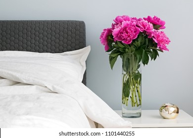 Bed with white bed sheets and pink peonies on the nightstand. Modern bedroom detailts.