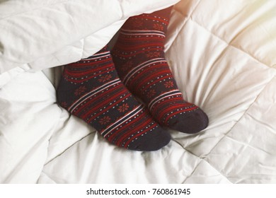 In bed, women's feet in socks with ornament.
