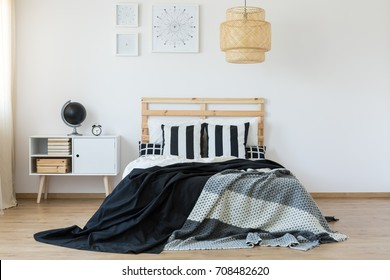 Bed with wooden bedhead in black and white bedroom