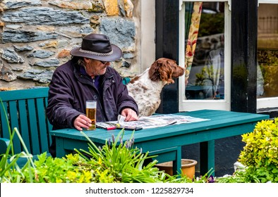 BEDDGELERT / WALES - MAY 03 2018 : Man and dog enjoying the traditional town.