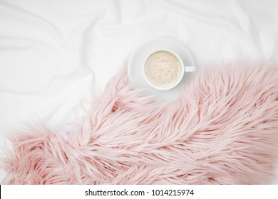 Bedding with a pink fluffy fur plaid and cup of coffee. Copy space. Flat lay, top view