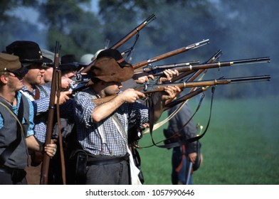 Bedford Bedfordshire England 1993. A group of unidentified reenactors of the American Civil War wear period clothing of Confederate sharpshooters firing their rifles at a re-enactment event.
