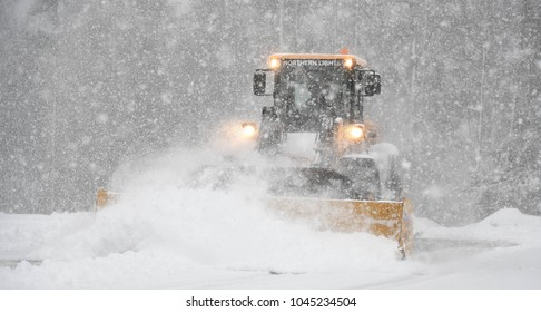 Bedford, N.H., USA, March 13, 2018. A town snow plow clears the high school parking lot for voters on town election day.