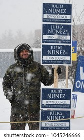 Bedford, N.H., USA, March 13, 2018. Town Council candidate Julio Nunez campaigns outside the polling place during a snow storm on  town election day.