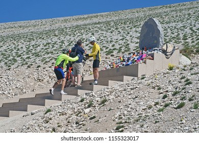 Bedoin, Mont Ventoux, France - June 26, 2018: Cyclists always stop at the monument of Tommy Simpson in Mont Ventoux to place their bidon as remembrance
