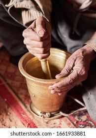 Beduinenmahlende Kaffeebohnen für traditionellen Gutenkaffee mit Gewürzen