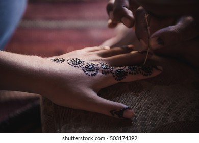 Bedouin making henna on a woman's hand. Hand decorations are usually done by a relative of the bride in her home