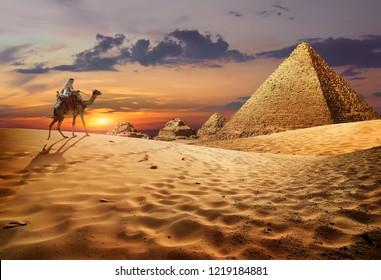 Bedouin on camel near pyramids in desert