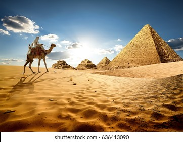 Bedouin on camel near pyramids in desert