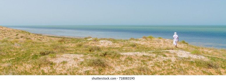 Bedouin in white robe overlooking the Atlantic ocean from dunes in Banc d Arguin National Park, Mauritania, North Africa