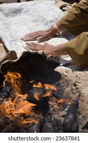 Bedouin woman is kneading dough for bread with burning fire in the foreground.