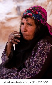 Bedouin woman smoking a cigarette in Petra, Jordan; February 26, 2010