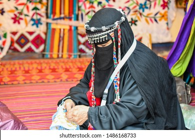 Bedouin Woman wears traditional Arabic Clothes doing kraft hand made Sado in Hijin festival activity in Taif City in Saudi Arabia. Mawsim Al Taif