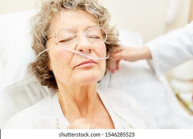 Bedridden senior with oxygen goggles or nasogastric tube in nursing