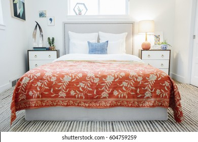 A bedroom in an apartment with a double bed and beside cabinets, and a vivid russet coloured bedspread with a floral pattern