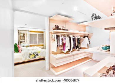 Bedroom attached to the garment store room of a house with ladies and gents shirts  hanging under the racks and shoes on the shelves beside the bedroom door entrance