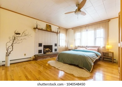 Bedroom with big bed and fireplace at day light