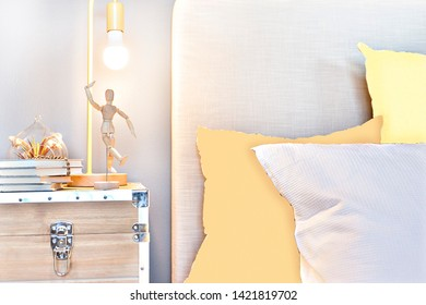Bedroom with blankets and pillows beside wooden doll dancing on the box with silver locks under the yellow and flashing lamp near to the wall, the cushion of the bed lean to wall