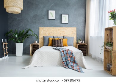 Bedroom with concrete wall, bed, lamp and plants