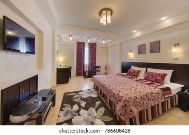 The bedroom with a dark carpet on a floor, the TV, a table and a window