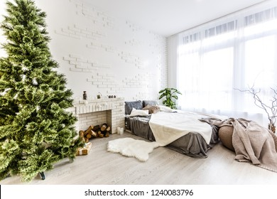 The bedroom decorated by Christmas. Cozy light interior: plaid, wooden bed In the room there is a New Year's fir-tree decorated with toys and garland