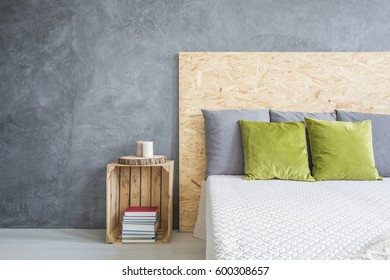 Bedroom with decorative wall finish, OSB headboard and crate nightstand