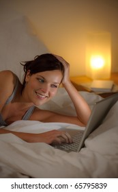 Bedroom evening - woman with laptop lying down in bed