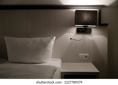 Bedroom fragment. Pillow, blanket, sconce, flexible reading light and bedside table / nightstand. Sample of bedside area lighting. Abstract modern interior fragment in dim light.