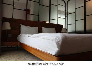 Bedroom with glass walls and double bed. Bed with wooden sides.