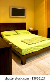 Bedroom with green double bed and picture frame
