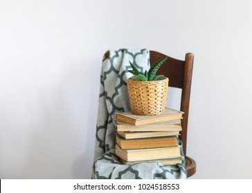 Bedroom interior close up with green plaid, books and plant on a chair. Home interior vintage decor